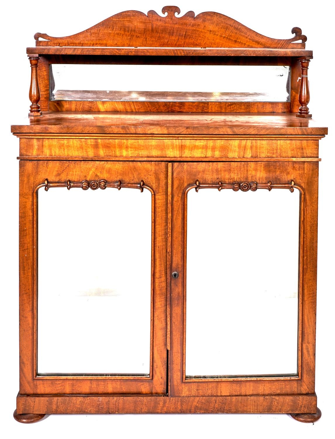 A Victorian mahogany chiffonier, the lower part enclosed by mirrored doors, on turned bun feet,
