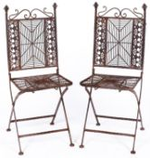 A pair of cast metal garden chairs, the ornate s-scroll top rails above spider's web splats