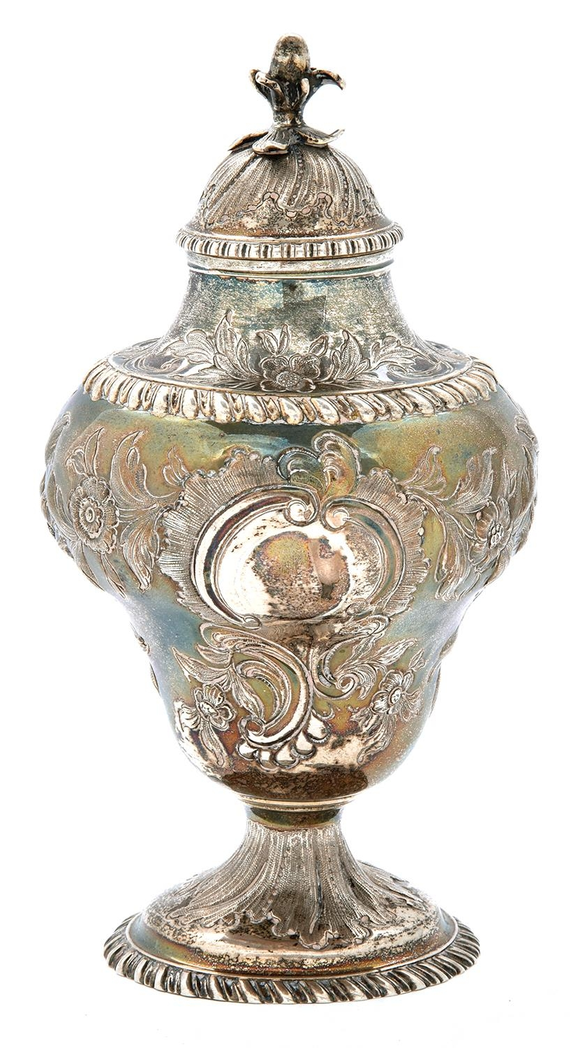 A George III silver tea caddy and cover, of pear shape, crisply chased with an eagle, flowers and
