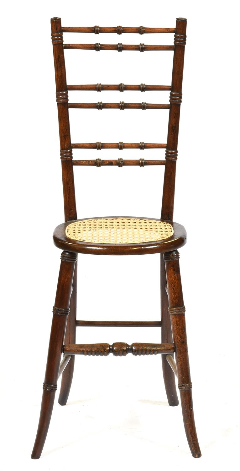 An early Victorian stained beech child's correction chair, with caned seat, seat height 49cm