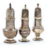 A George II silver sugar caster and cover and a pair of George III silver pepper casters and covers,