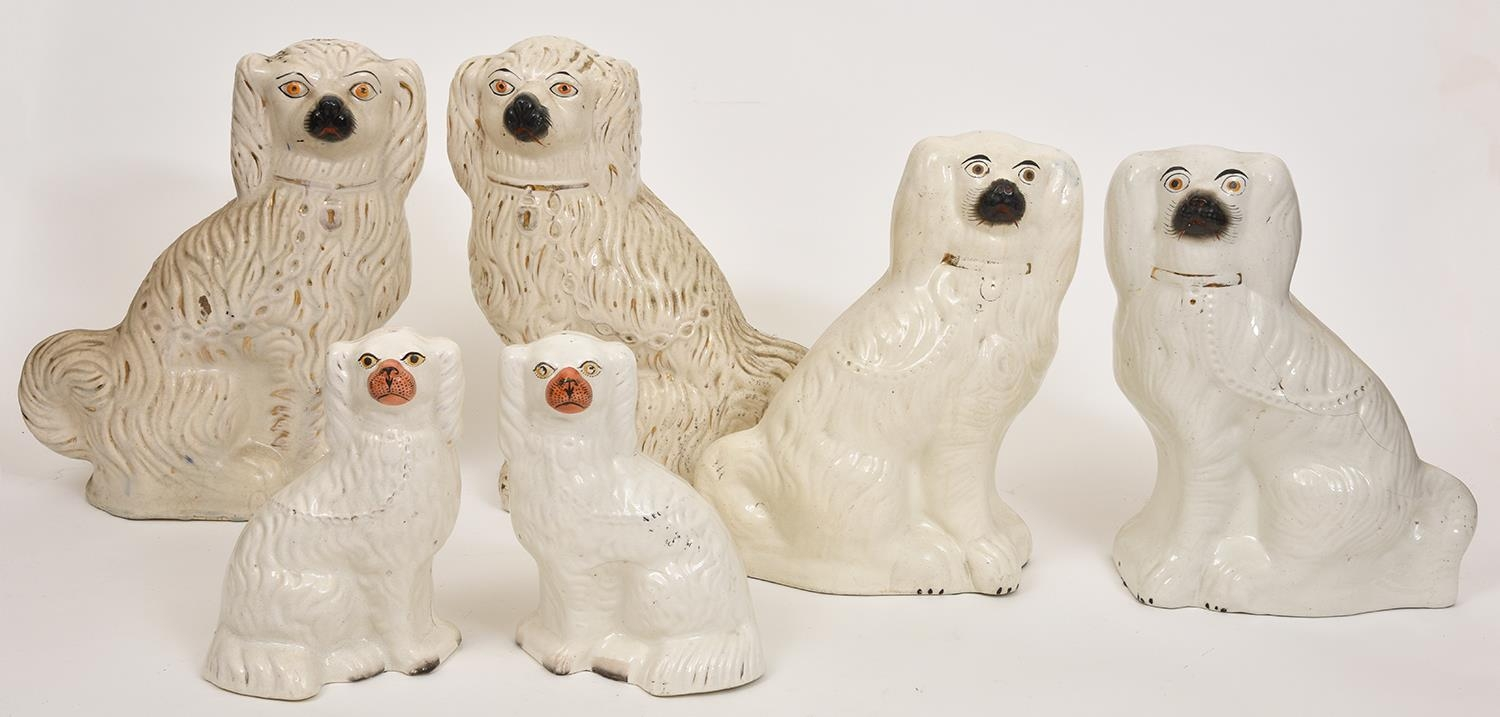 Three pairs of Staffordshire earthenware models of spaniels, late 19th c, 39cm h and smaller Typical