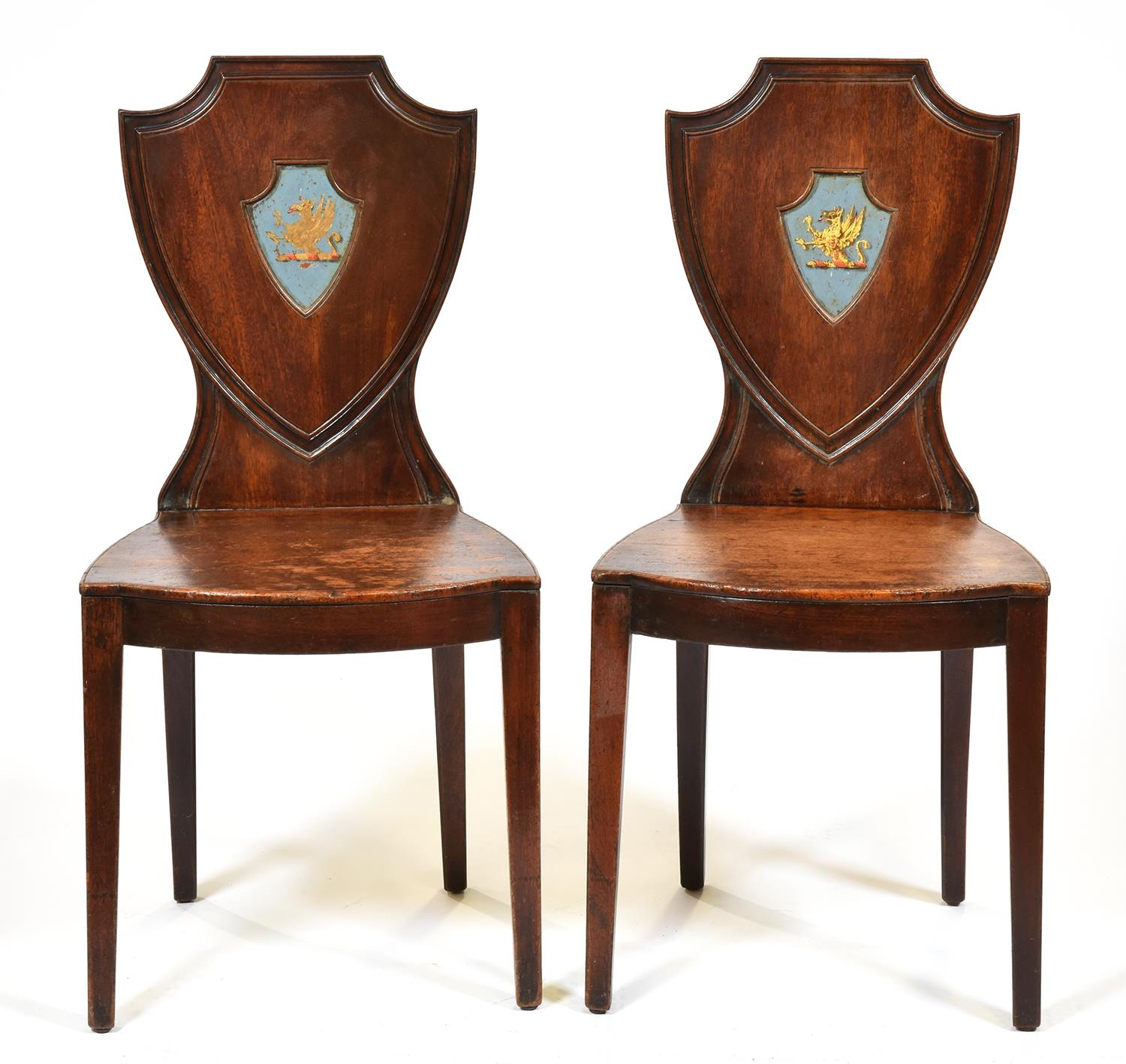 A pair of George III mahogany hall chairs, late 18th c, the shield back painted with the crest of