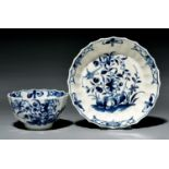 A Worcester fluted tea bowl and saucer, c1770, painted in underglaze blue with the Hollow Rock