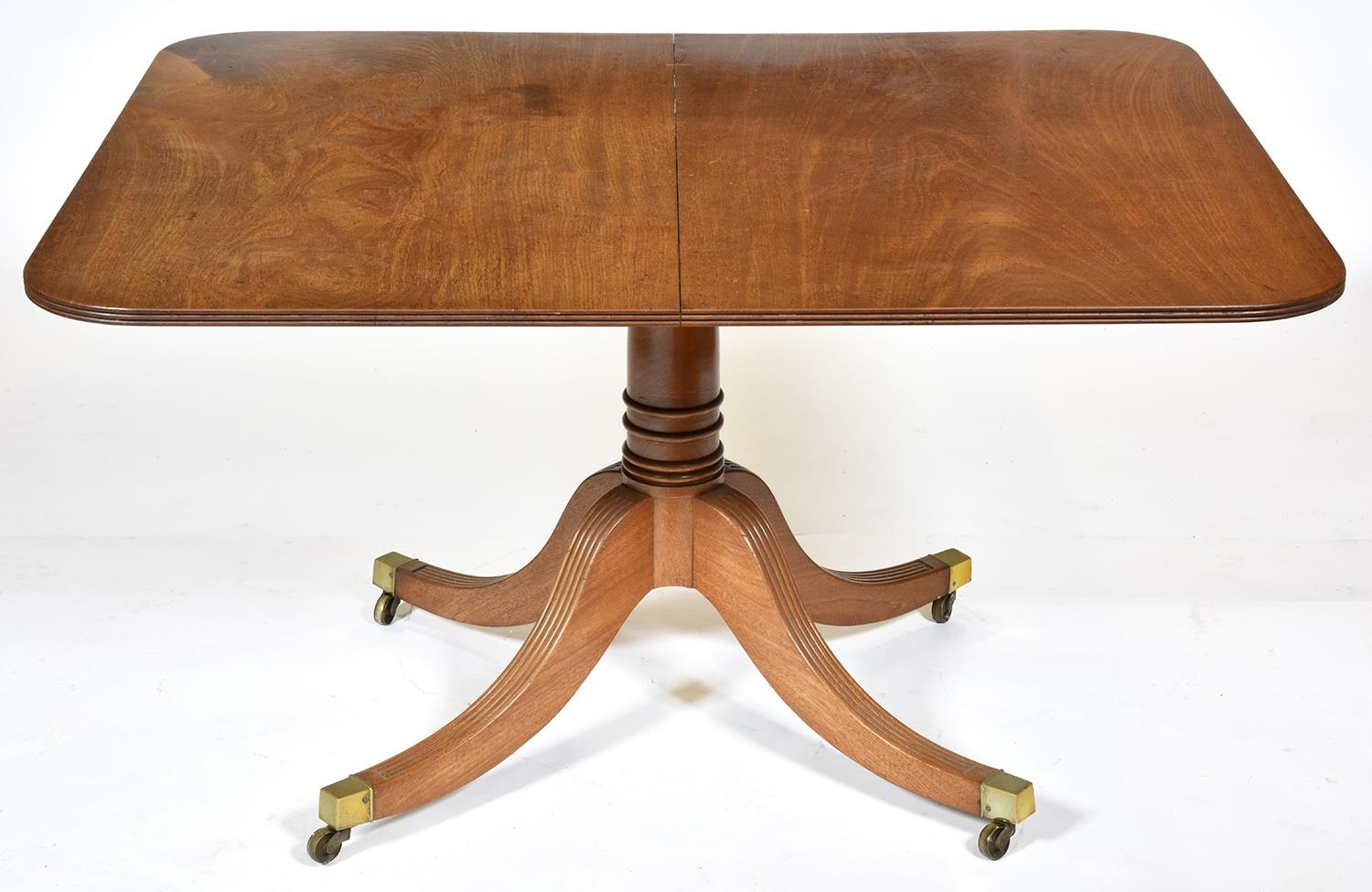 A GeorgeIV mahogany breakfast table, c1825, the oblong tip-up top on ring turned pillar and