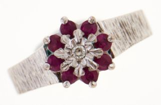 A ruby and diamond cluster ring, in white gold with textured shoulders, marked 18ct, 4g, size J Good
