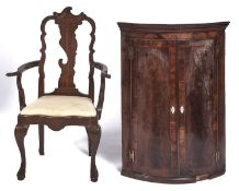 A George III bow fronted mahogany and crossbanded hanging corner cupboard, early 19th c, with
