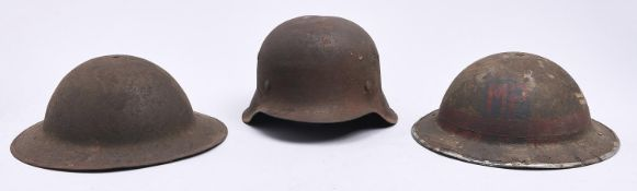 A German, Third Reich soldier's steel helmet and two contemporary British military steel helmets,