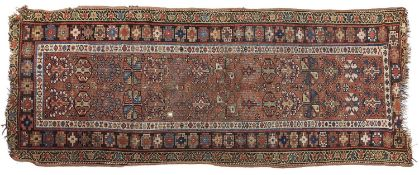 An antique red ground rug - 103 x 265cm Wear and losses at ends