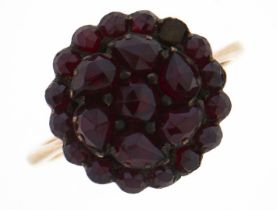 A garnet cluster ring, c1900, gold coloured metal hoop, 2.8g, size L One stone deficient, light wear