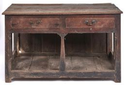 An oak dresser, 18th c, with boarded top and fitted two drawers, the brass handles apparently