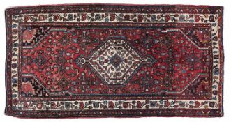A Caucasian style red ground rug, 87 x 192cm Good condition but for requiring a clean
