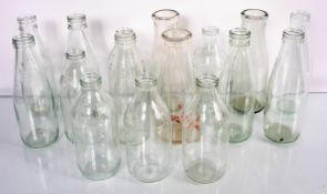 A collection of sixteen glass milk bottles. Tallest measures; 23cm.