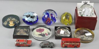 A collection of assorted glass paperweights to include some pictorial examples,