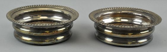 A pair of silver plated wine coasters retailed by Harrod's, mahogany base,