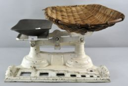 An enamelled set of cast iron shop scales with wicker basket,