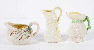 Three Belleek parian jugs, comprising : a shell shaped example,