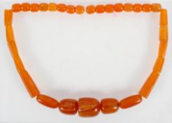 A large graduated orange bead necklace, strung plain with no clasp.