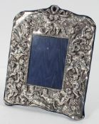 A Britannia standard silver photo frame, decorated overall with Putto , maker NLS,