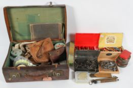A large box and a leather suitcase containing fishing related equipment,