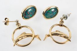 A yellow metal pair of drop earrings stylized as a dolphin with a pair of opal triplet stud earrings