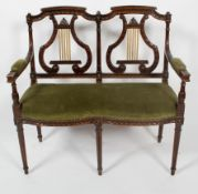 A Regency style two seat canape, with lyre back rests, serpentine seat and tapering fluted legs,