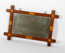 An Arts and Crafts style mirror with a notched wooden frame,
