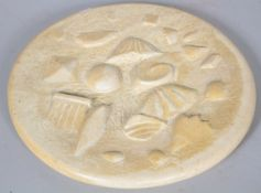 A carved and part polished stone roundel, incised PM89 to base,