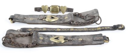 A collection of horse brasses on leather straps,