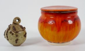 A Poole pottery style biscuit barrel, glazed in flowing orange,