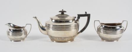 A silver three piece tea service, of oval ribbed and fluted form, the teapot with domed cover,