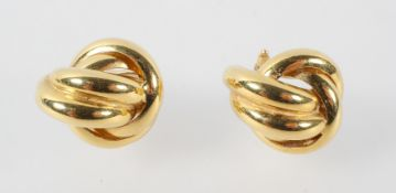 A yellow metal pair of large knot style earrings with post and clip fittings.