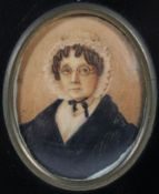 An early 19th century miniature of an elderly lady, in ebonised frame,
