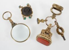 A collection of three seal fobs together with a watch key, and abstract link and a magnifying glass.