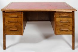 A mid 20th century vintage golden oak twin pedestal desk having a red leather top,