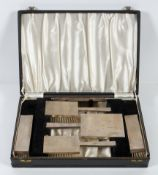An Art deco style silver mounted dressing table set, comprising brushes, hand mirror and comb,