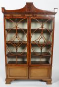A George III mahogany display cabinet with glass front, flowing pediment,
