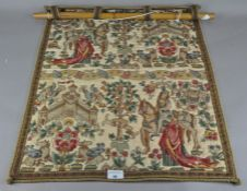 A wall hanging depicting a traditional scene,