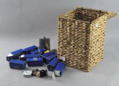 A wicker lidded basket containing a mixed assortment of items,