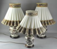 A pair of Japanese style table lamps, ceramic, and a smaller example, all with shades,