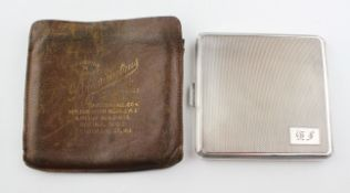 A hallmarked silver cigarette case, the outer with engine turned decoration,