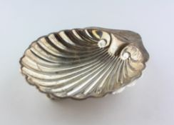 A George V silver butter dish, of shell form, raised upon three ball feet,