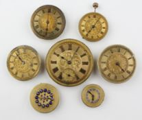 A collection of seven mechanical watch movements with dials attached.