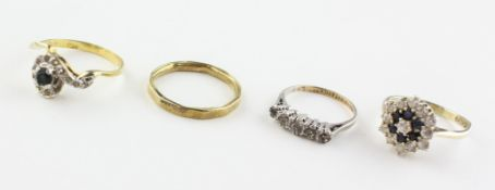A collection of four dress rings. Three are marked for silver of variable standards.