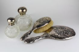 A matched silver backed dressing table set, with Reynolds cherubs decoration,