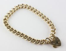 A yellow metal curb link bracelet with padlock and safety chain. Hallmarked 9ct gold, Birmingham.