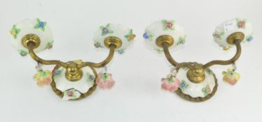 A pair of unusual ceramic wall sconces, adorned with floral decoration,