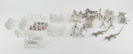 A collection of silver plated knife rests of varying shapes and sizes,