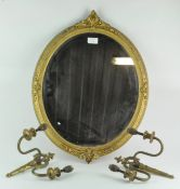 An ornate gilt framed mirror of oval form, 58cm x 45cm; together with a pair of brass wall lights,