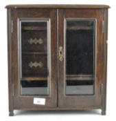 An early 20th century oak smoker's cabinet, the two doors with bevelled edged glass panels,